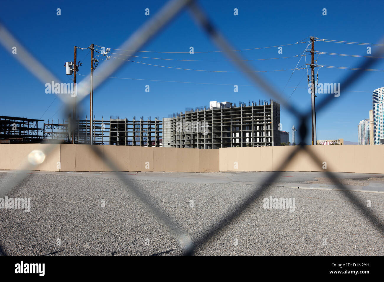 chain link fence around empty vacant unused lot looking towards unfinished echelon on the Las Vegas strip Nevada - Stock Image