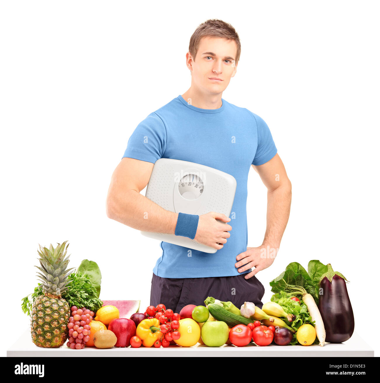 A male athlete holding a weight scale behind a table full of fruits and vegetables isolated on white background Stock Photo