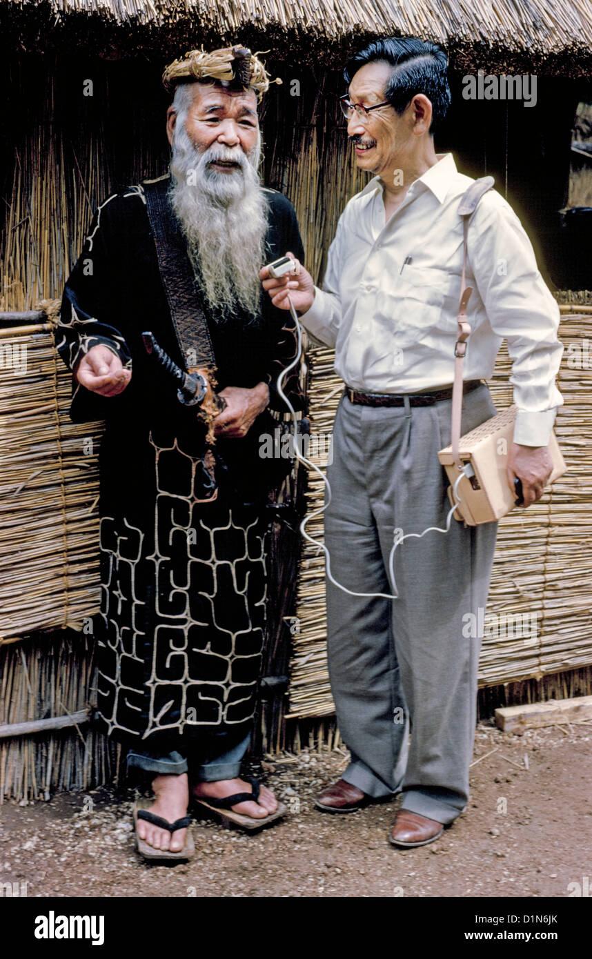 Japanese linguist Professor Kyosuke Kindaichi tape records the stories of a bearded Ainu village chief in Hokkaido, - Stock Image
