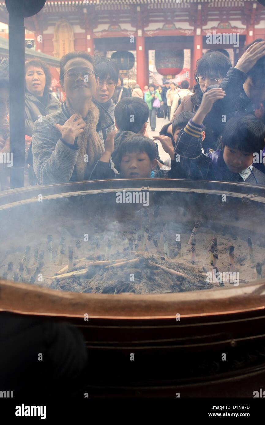Inhaling incense smoke in Tokyo - Stock Image