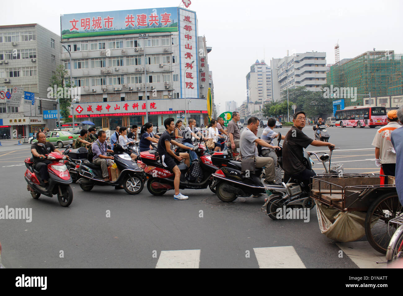 chinese waiting in a traffic light on minibike moped a road in chengdu china - Stock Image