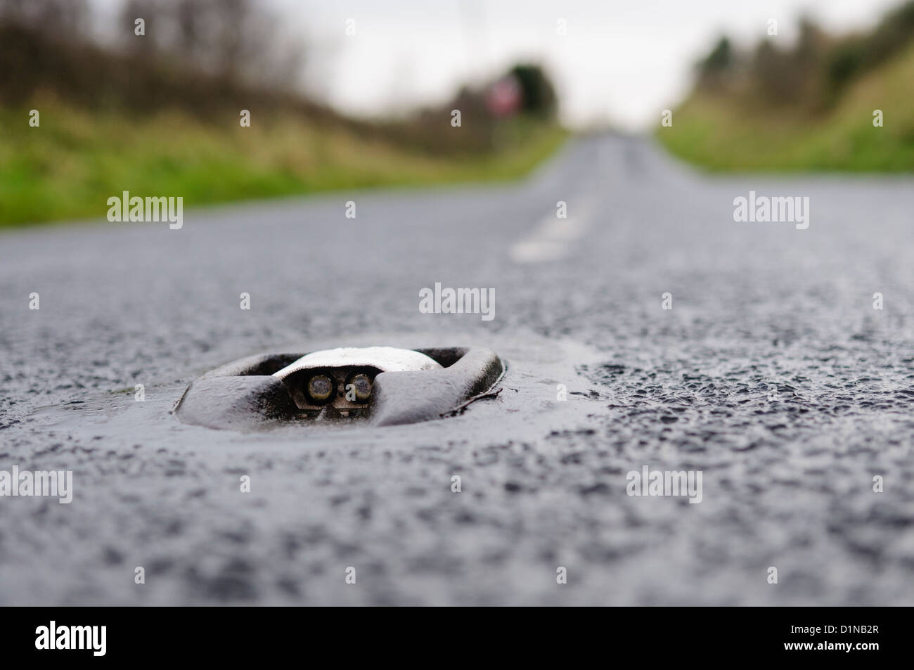 Catseye (TM) reflective road marking in the middle of a rural road. - Stock Image