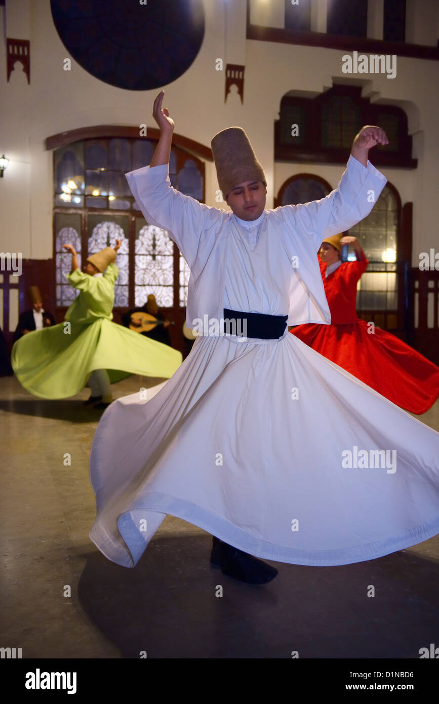 Male Sufi Whirling Dervish in white at a Sema Ceremony with musicians and women at Istanbul train station Turkey - Stock Image