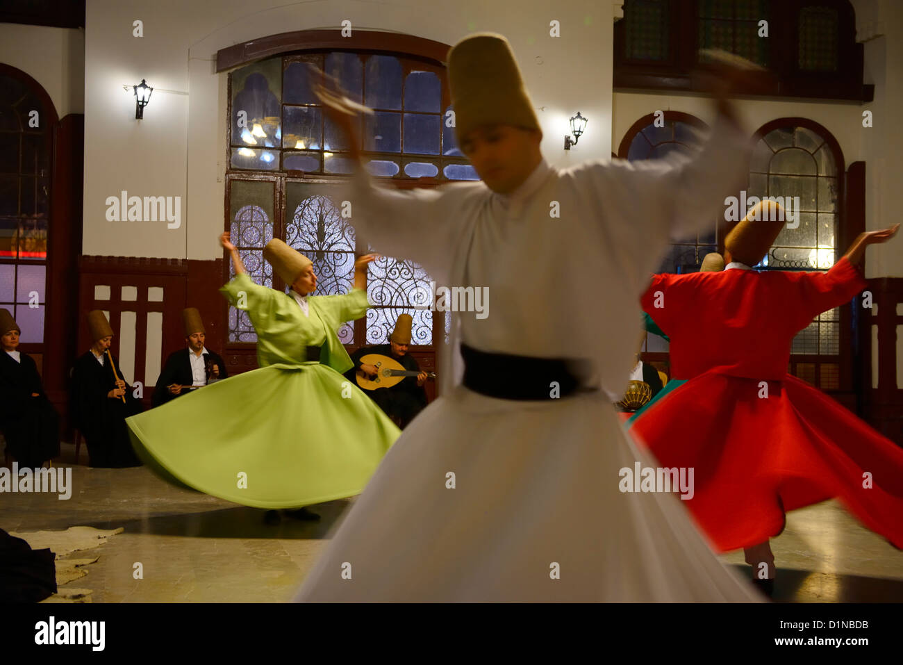 Spinning male and female Whirling Dervishes in a Sema Ceremony with musicians at Istanbul train station Turkey - Stock Image