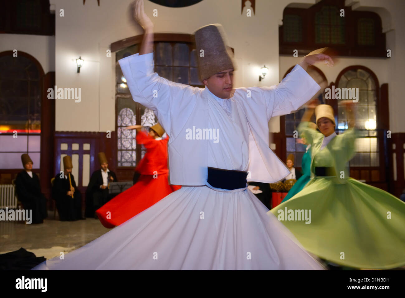 Male Sufi Whirling Dervish in a Sema Ceremony with musicians and women at Istanbul train station Turkey - Stock Image