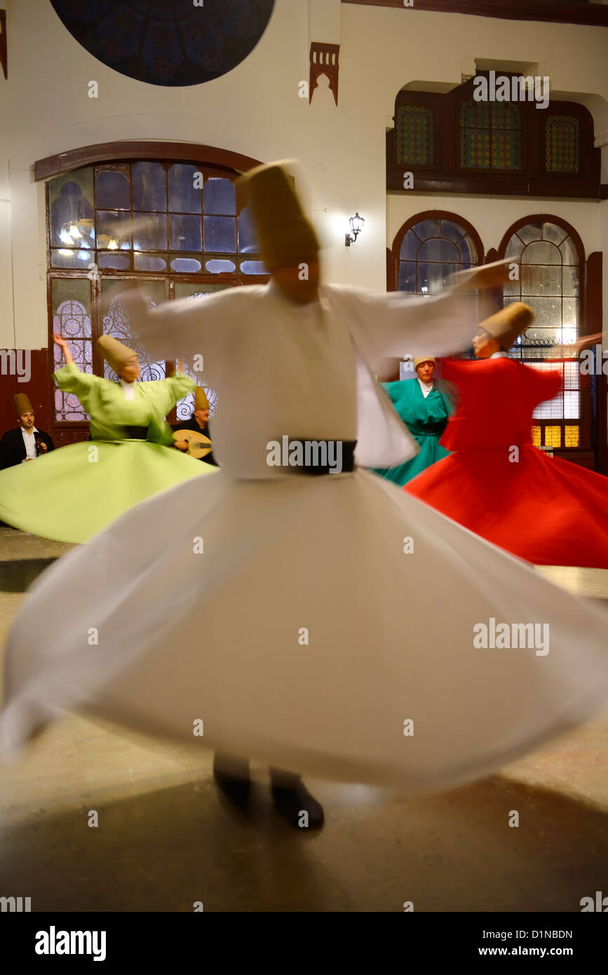 Spinning man with female Whirling Dervishes in a Sema Ceremony with musicians at Istanbul train station Turkey - Stock Image