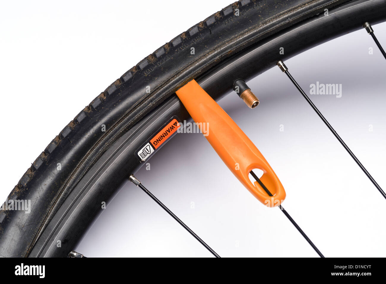Tyre lever removing a bicycle tyre - Stock Image
