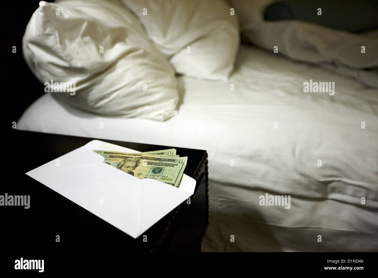 us dollars cash left in an envelope by the side of the bed in a hotel room in Las Vegas Nevada USA - Stock Image