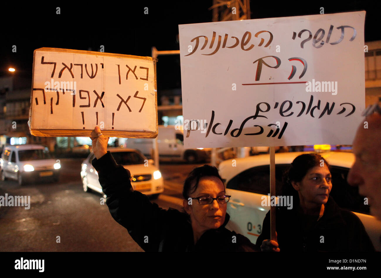 An Israeli woman holds a cardboard sign in Hebrew which reads 'This is Israel not Africa' during a demonstration - Stock Image
