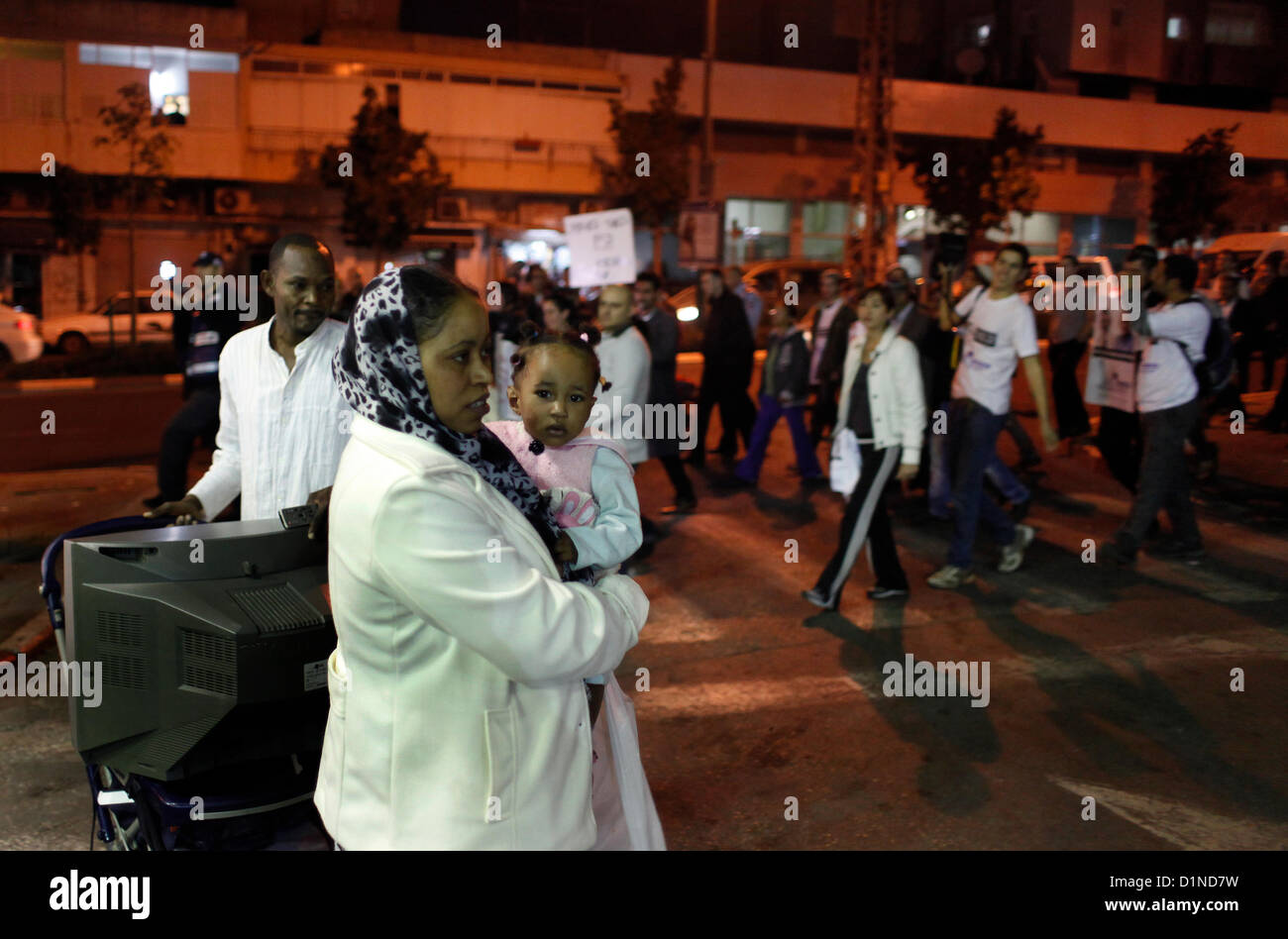 African migrant family pass an anti migrant protest in Tel Aviv in response to publication of an incident in which - Stock Image