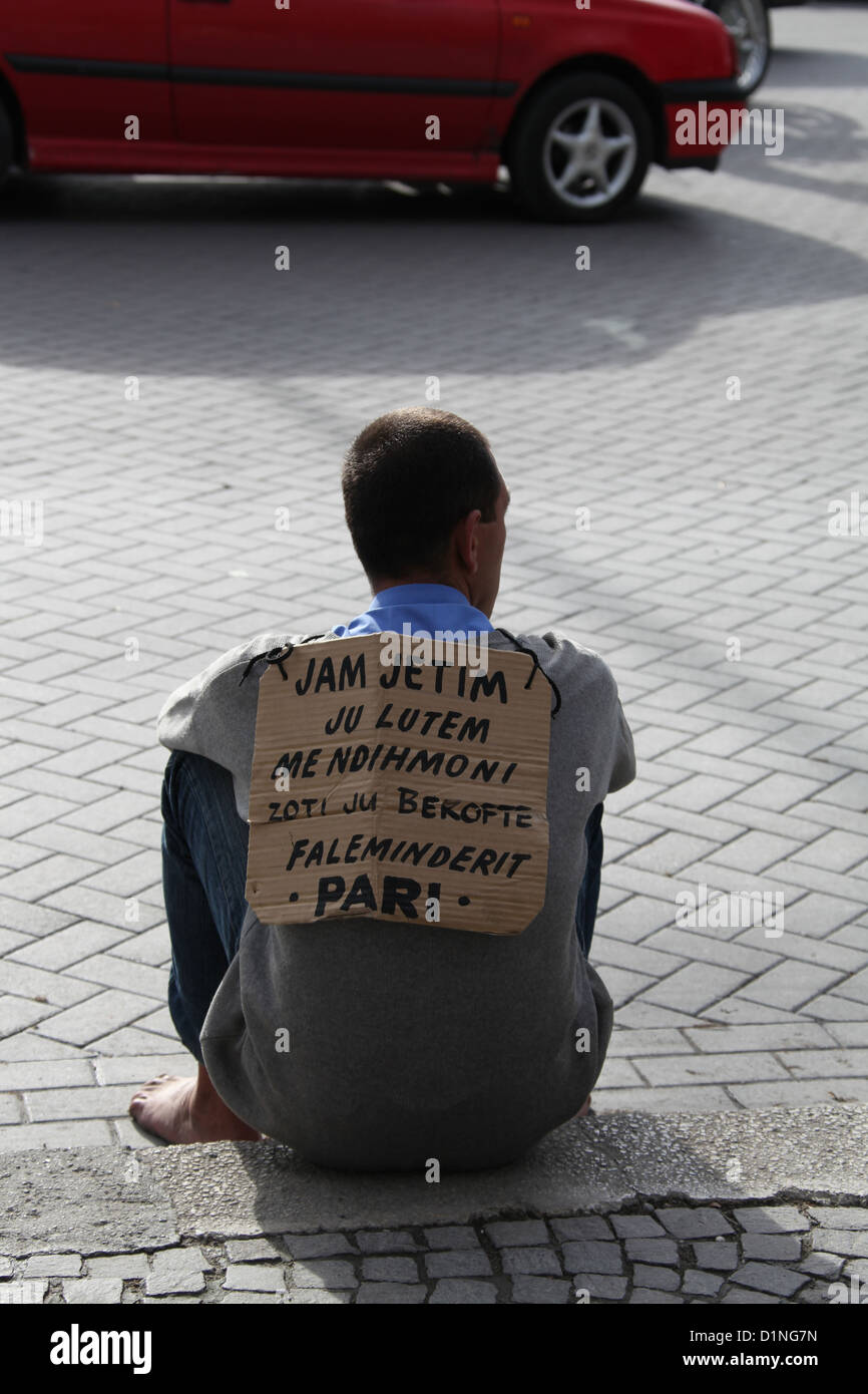 Man sitting on the pavement in Tirana wearing a cardboard sign - Stock Image