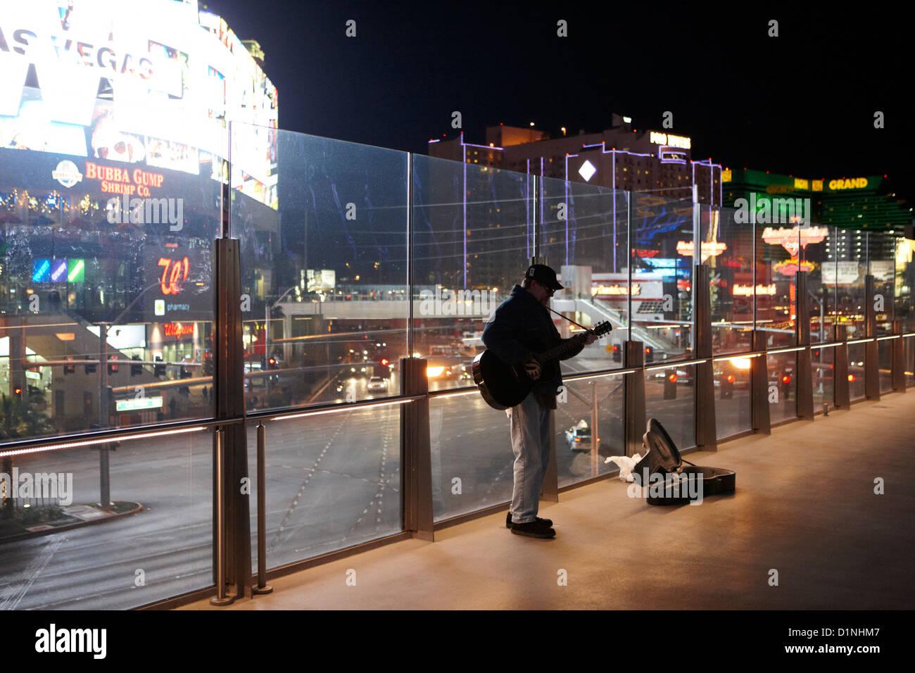 busker playing guitar on overhead walkway on Las Vegas boulevard Nevada USA - Stock Image
