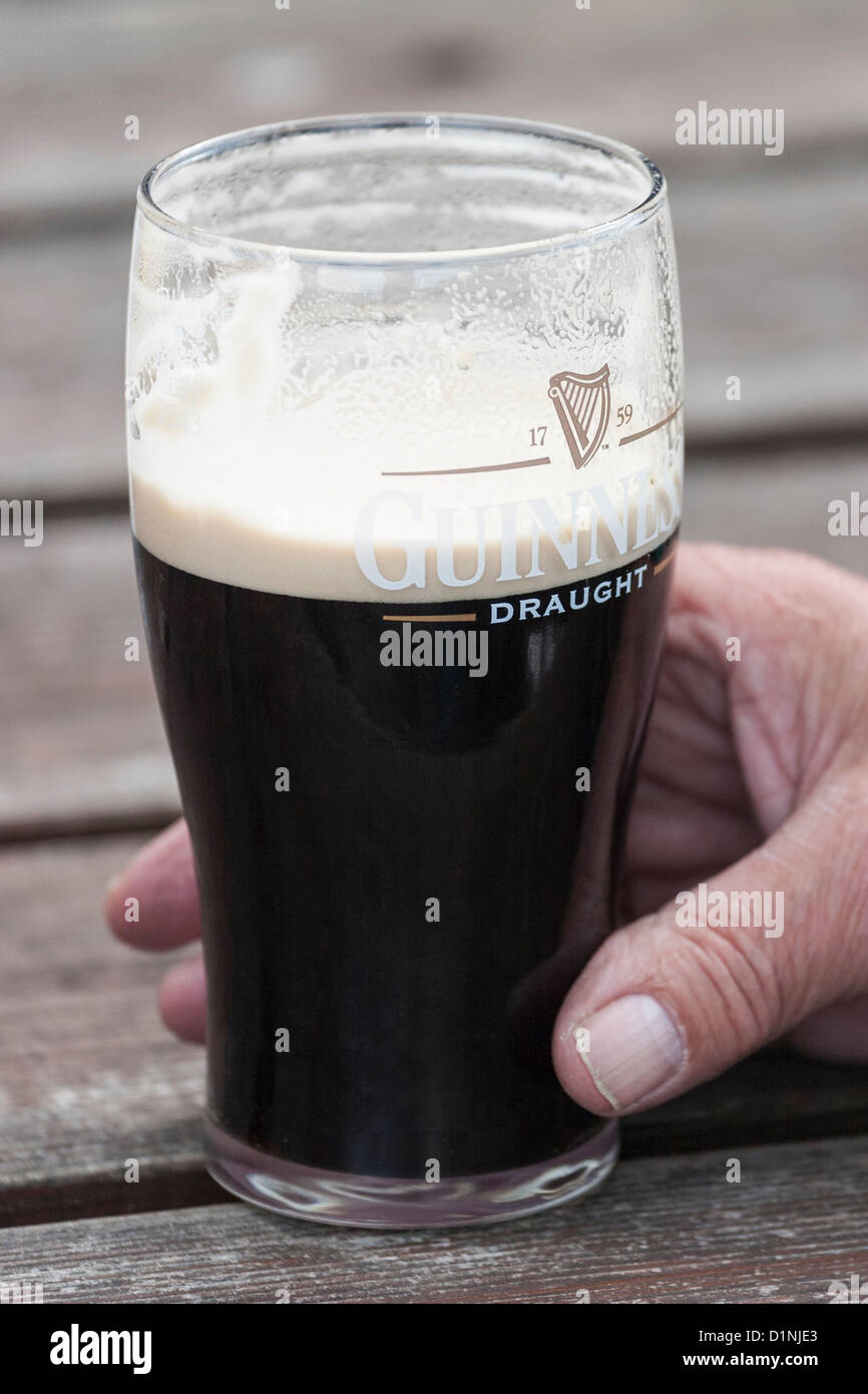 Guinness pint in his hand - Stock Image