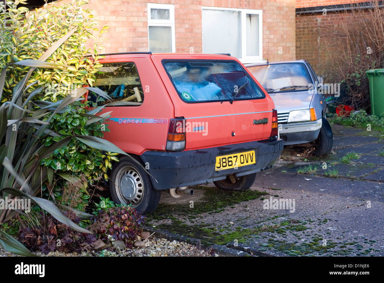 dilapidated cars used for storing junk in front of run down house ...
