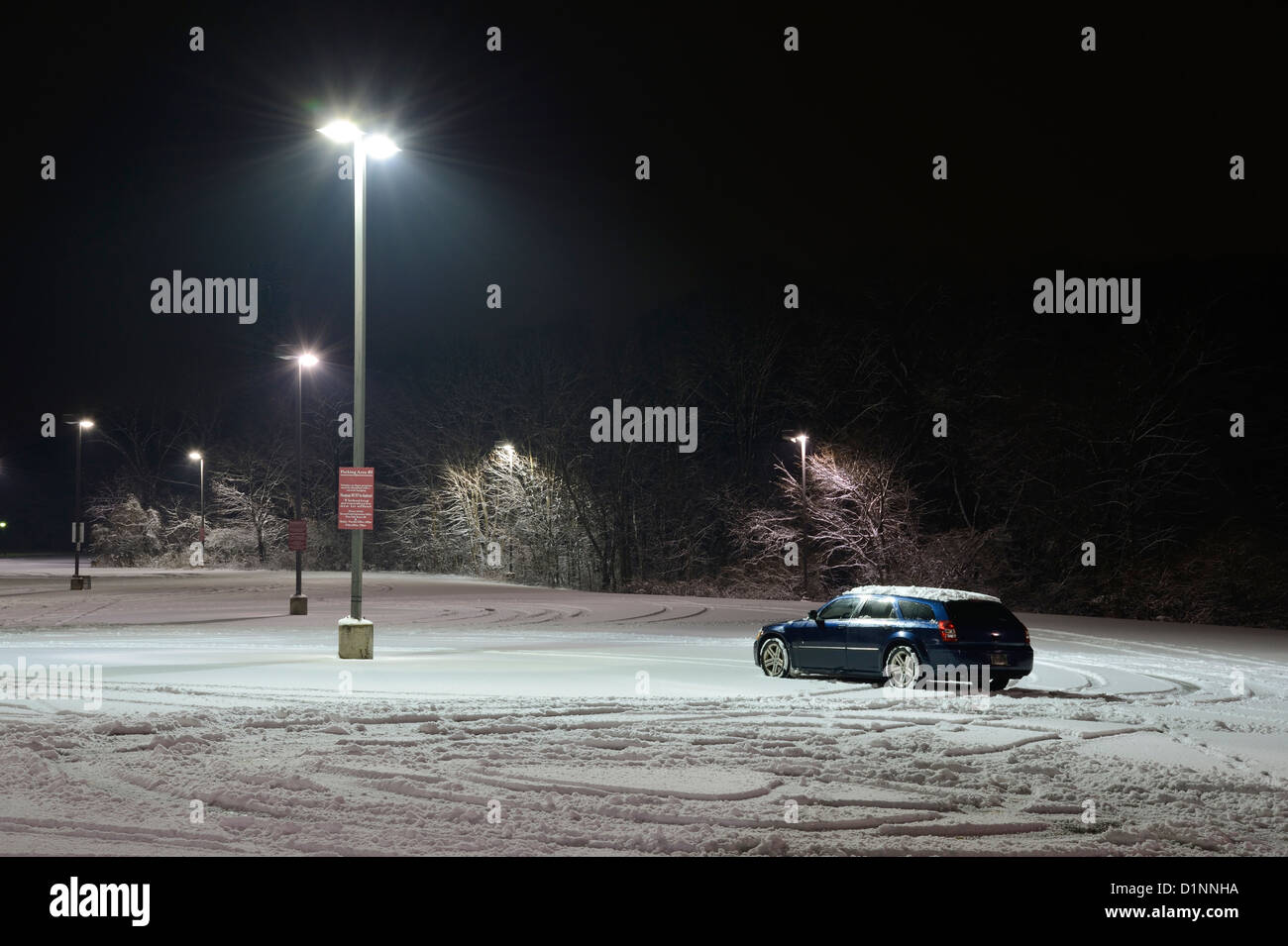 One Car In Lonely Snowy Parking Lot - Stock Image