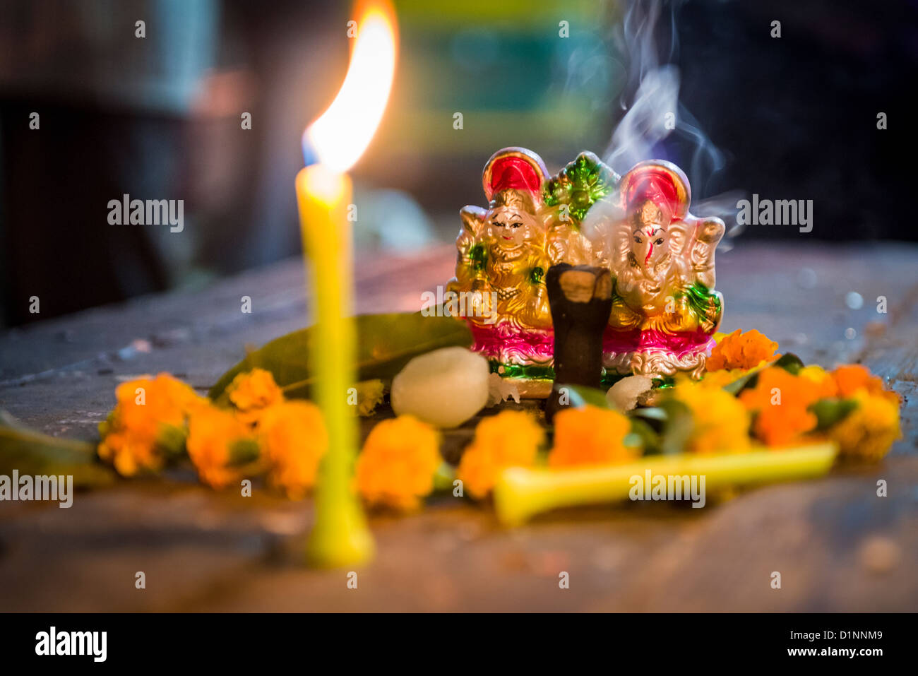 Indian deity statue on the table with Divali candle - Stock Image