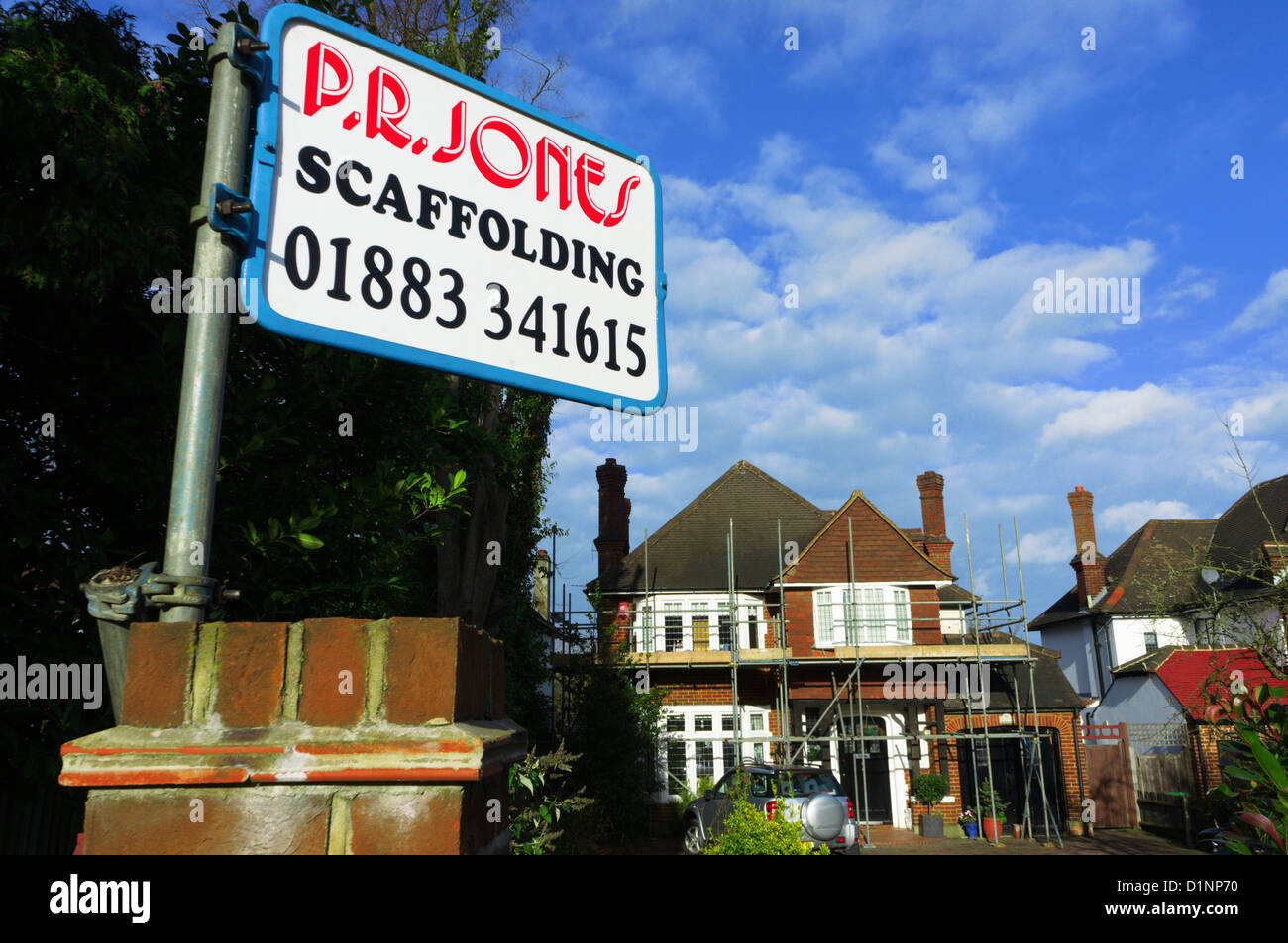 A scaffolding contractor's sign while work is carried out on a detached house. - Stock Image