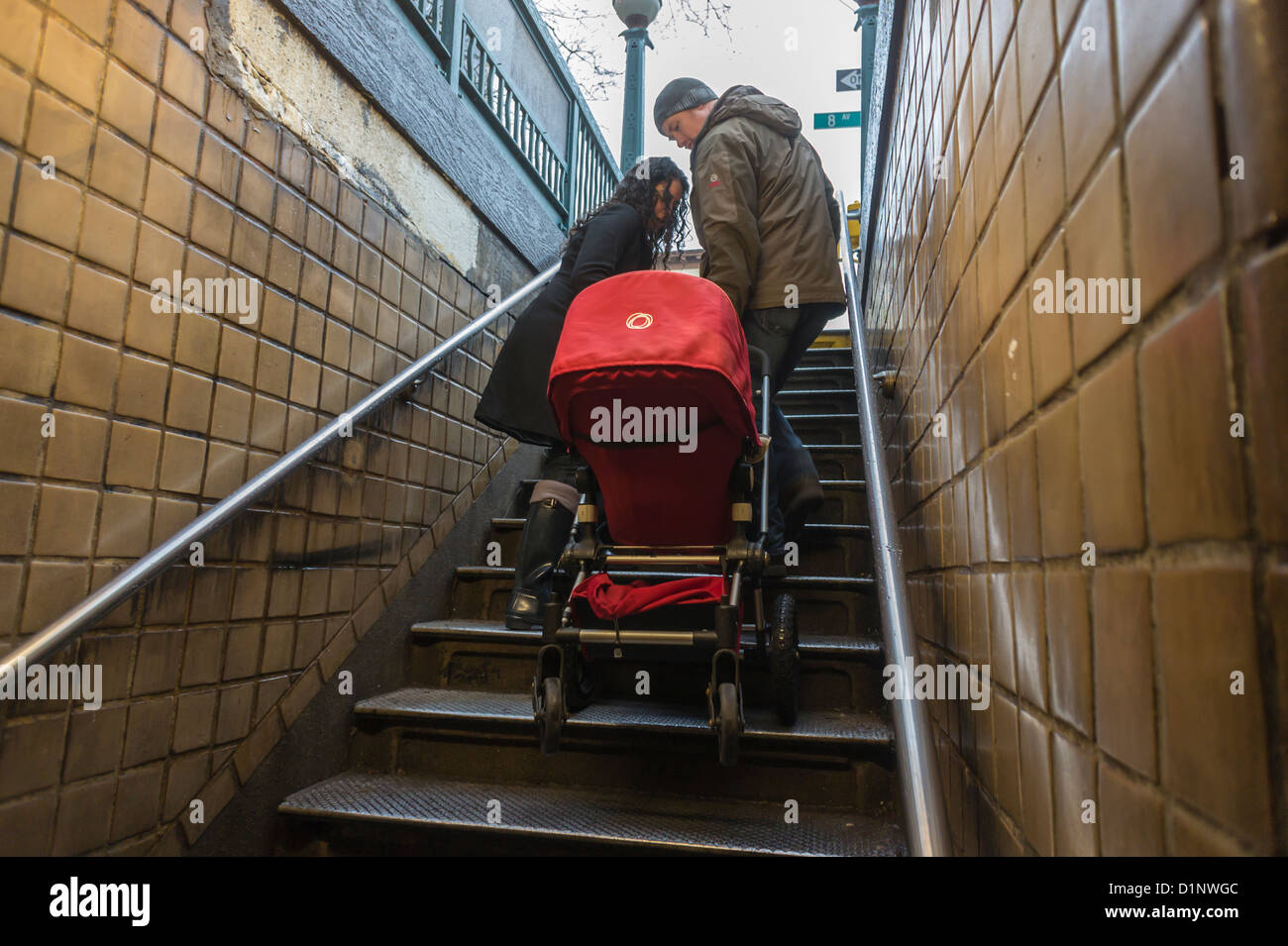 A Couple Carries A Stroller Up The Stairs As They Exit The