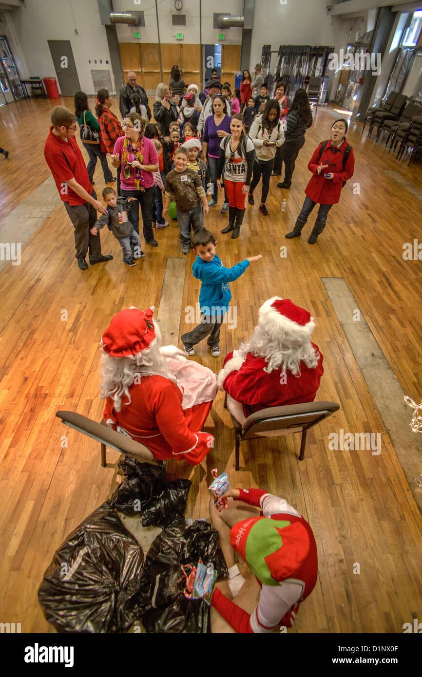 Deaf boy meets a deaf Santa Claus and Mrs. Santa using sign language at Christmas festivities at the California - Stock Image