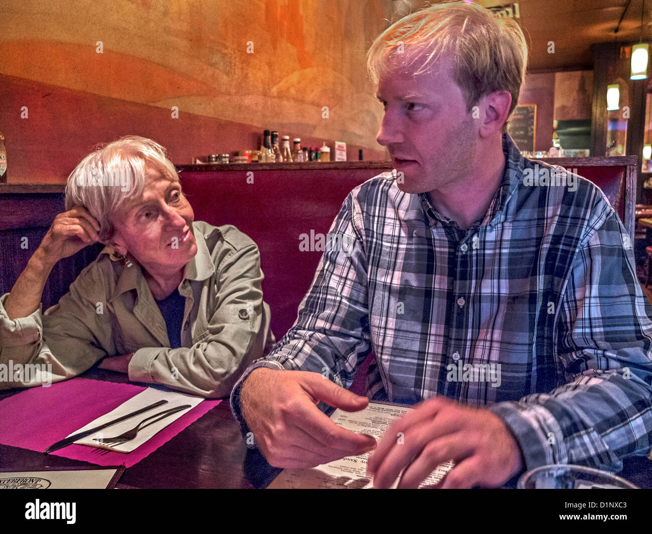 An older woman exemplifies the 'cougar,' a woman who favors a much younger man in Brooklyn, New York, restaurant. - Stock Image