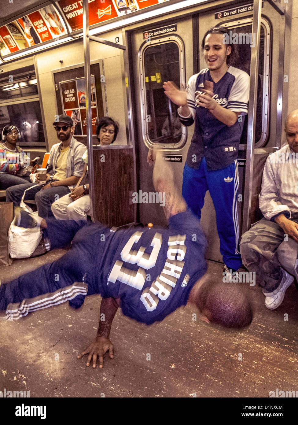 An African American man dances for passengers tips while riding in the New York City subway. Note partner. - Stock Image