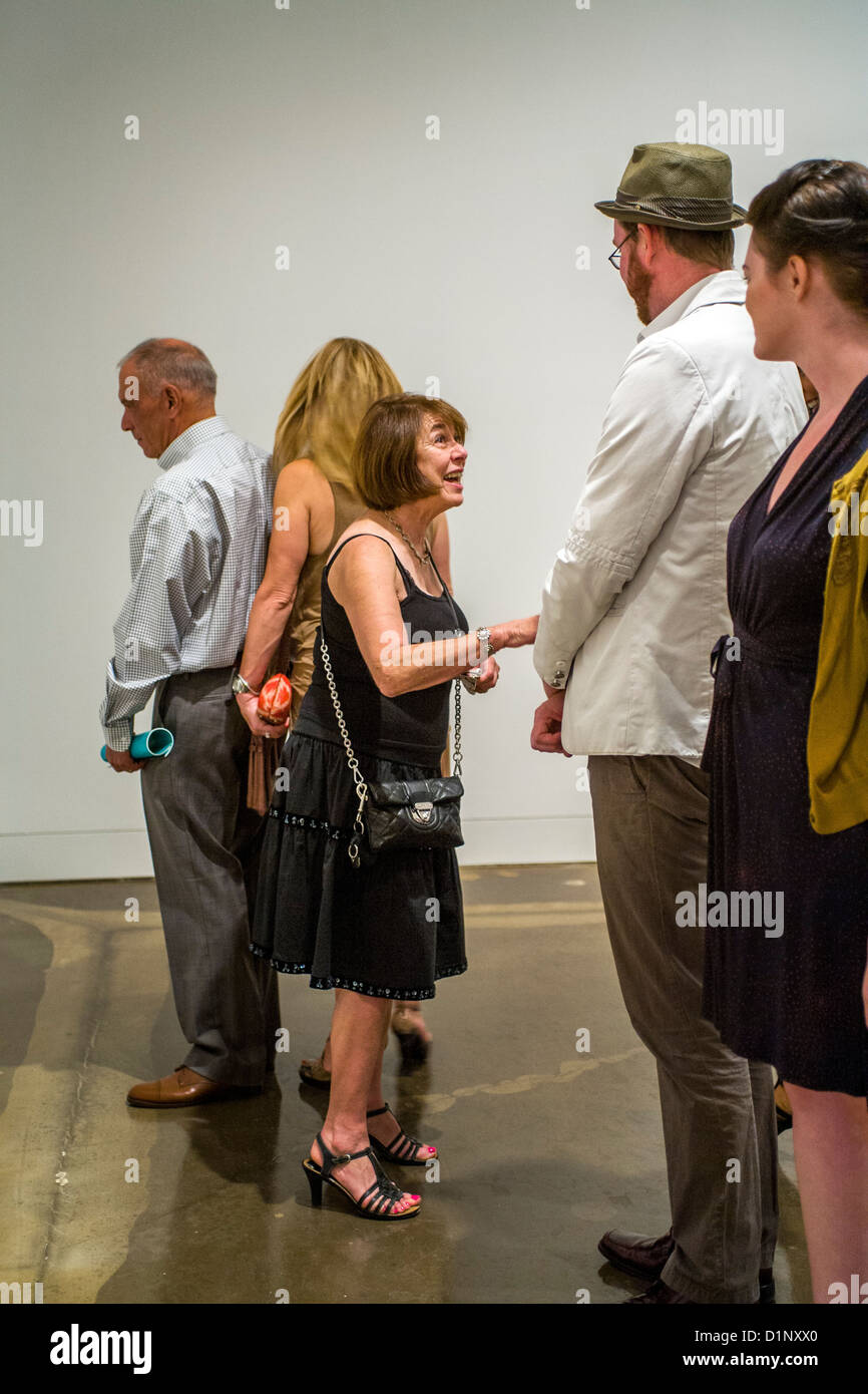 Invited guests talk at an art museum exhibition opening night and reception in Newport Beach, CA. - Stock Image