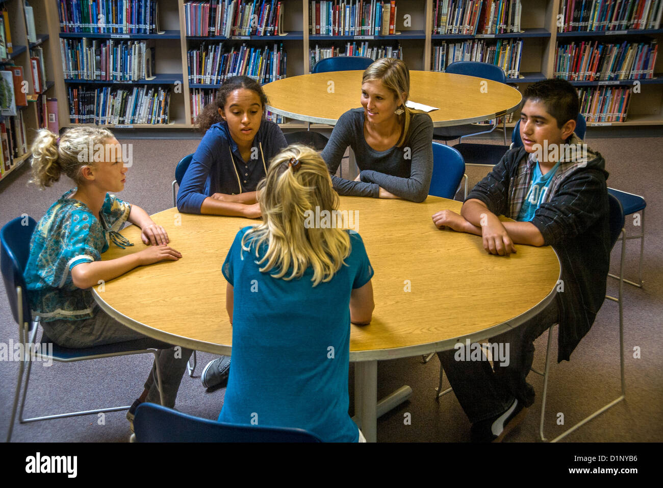 A junior high school counselor meets with a multiethnic group of students in a San Clemente, CA, school library. - Stock Image