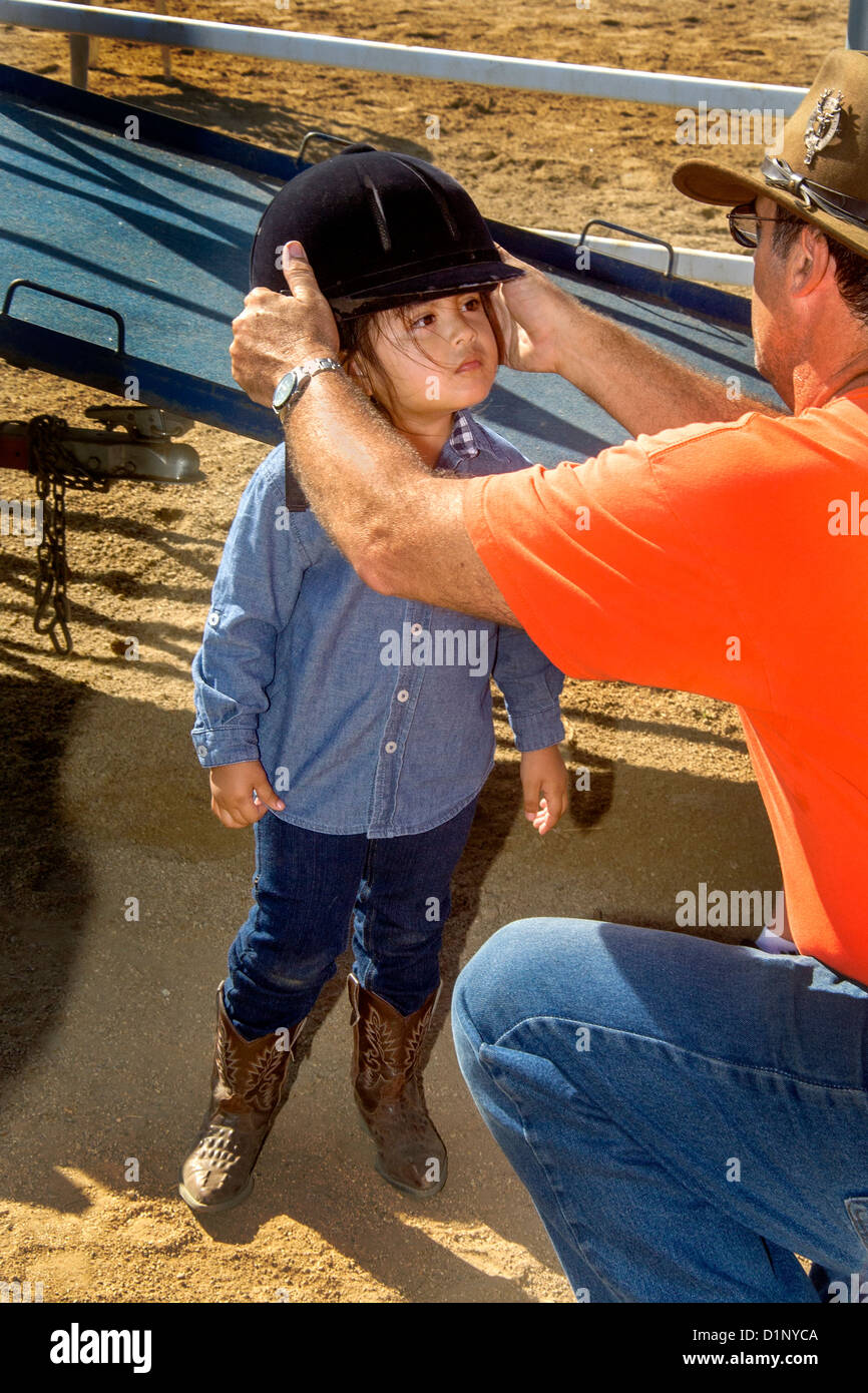 Hispanic girl suffering from speech delay is fitted for a safety helmet before riding a horse as part of therapeutic - Stock Image