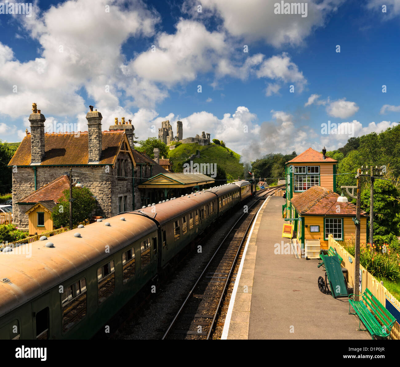 A steam train pulls in to the station at Corfe Castle in Dorset Stock Photo