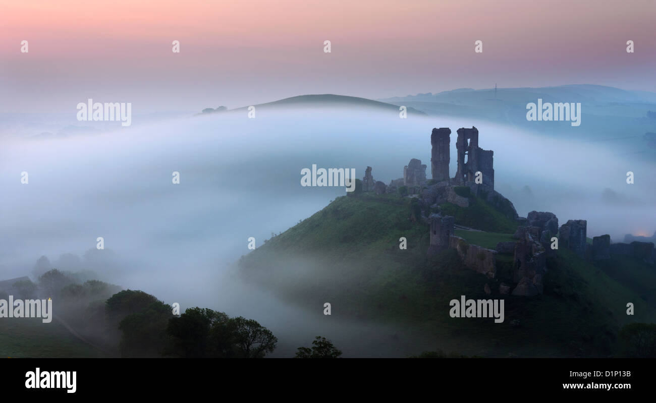The ruins of Corfe Castle in Dorset rise out of the mist. - Stock Image