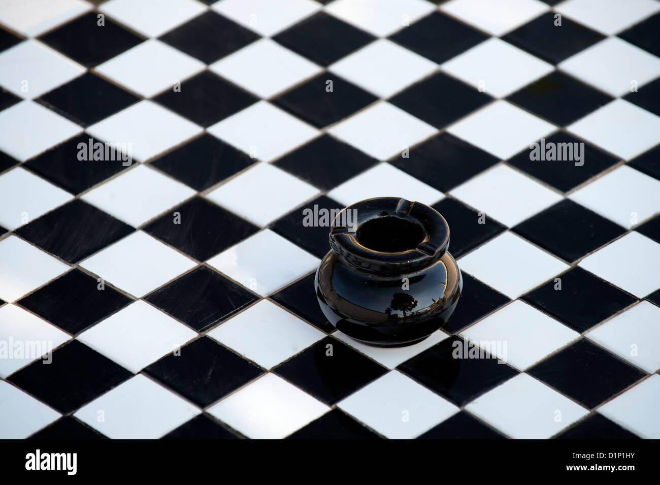Black ceramic ashtray on chequered or checkered black and white tiles table - Stock Image