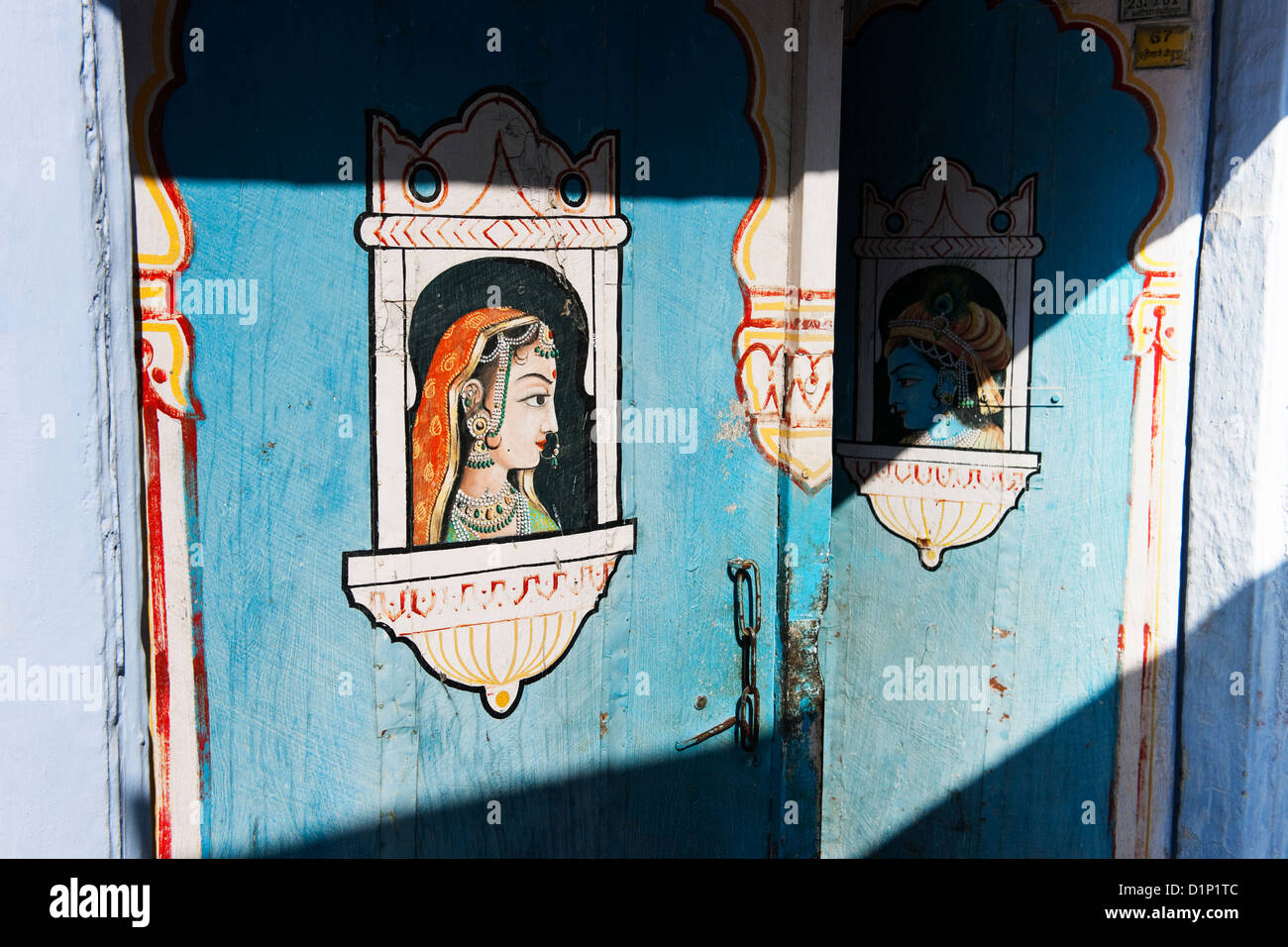A colorful door in the sun decorated in blue with Indian male and female deity shown as looking from windows towards - Stock Image