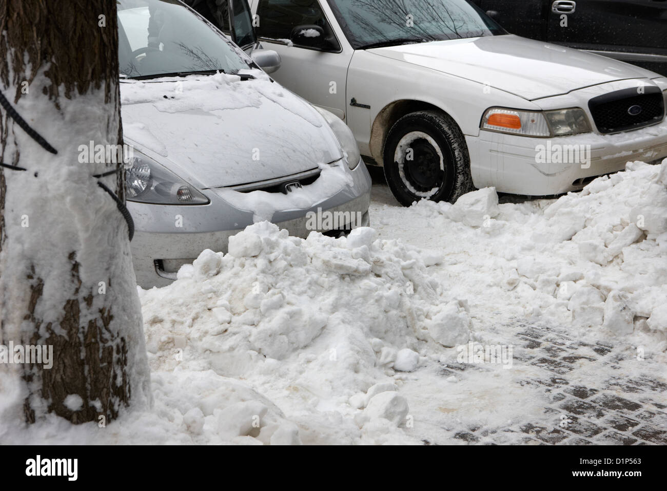 piles of snow cleared from sidewalk piled up at edge of sidewalk in front of parked cars Saskatoon Saskatchewan - Stock Image