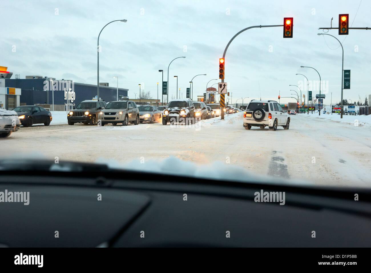 looking through car windshield at snow covered city intersection Saskatoon Saskatchewan Canada - Stock Image