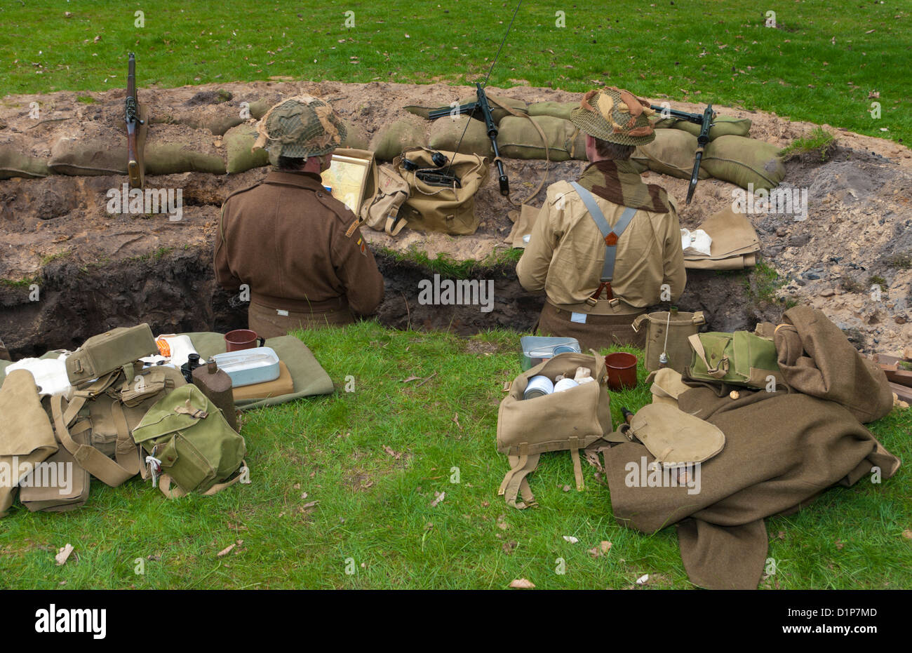 two soldiers in classic uniforms demonstratiing the life in a world war I trench - Stock Image