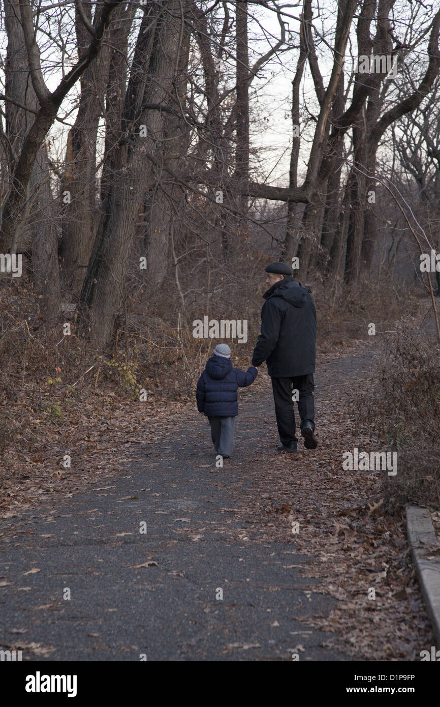 Grandpa and grandson walk among the trees in early winter in Prospect Park, Brooklyn, NY. - Stock Image