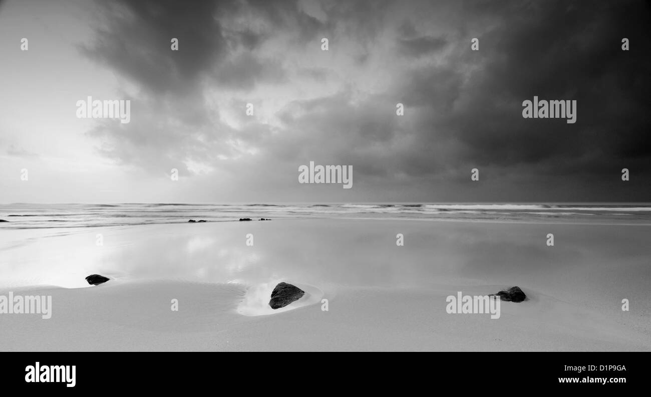 Peaceful black and white beach landscape with three stones under a blue stormy sky Stock Photo