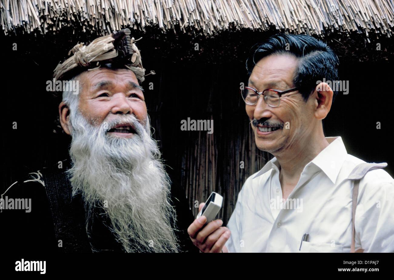 Japanese linguist Prof. Kyosuke Kindaichi tape records the stories of a bearded Ainu village chief in Hokkaido, - Stock Image