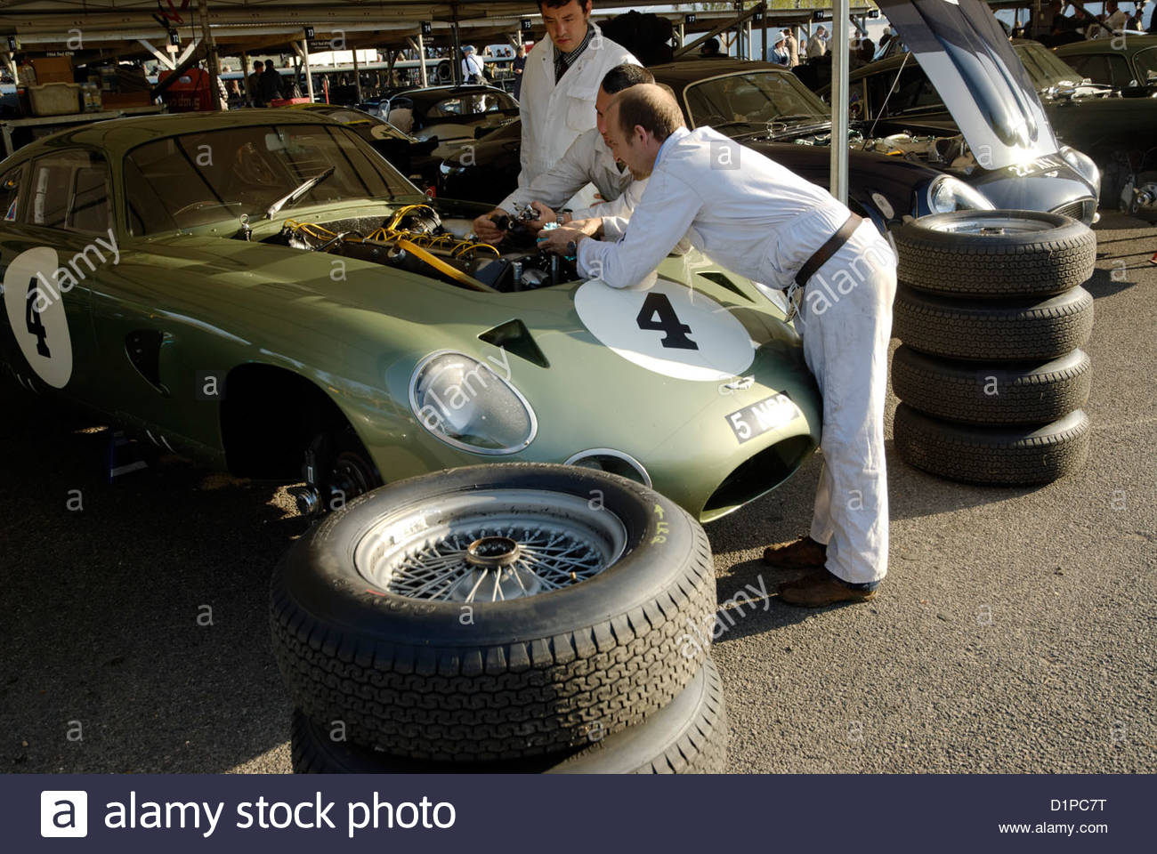 mechanics working on the engine of the 1963 Aston Martin Project 214 race car prototype - Stock Image