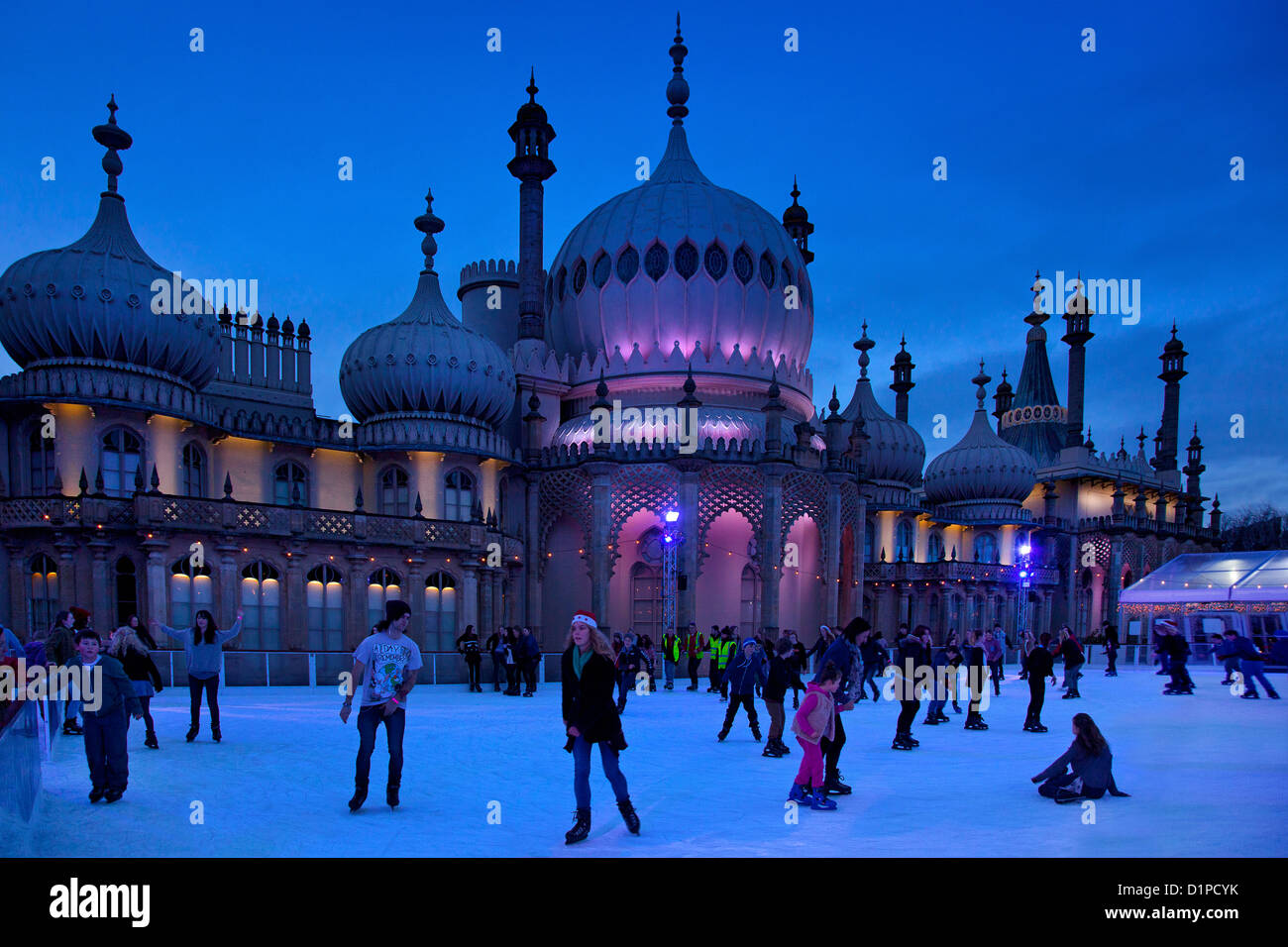 Brighton Royal Pavilion with winter ice skating rink and skaters at night, Brighton, East Sussex, England - Stock Image