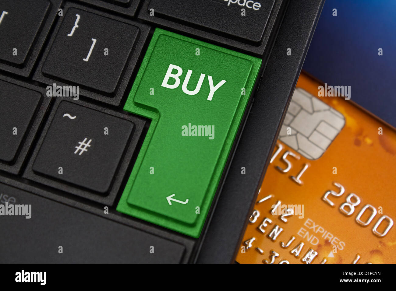 Buy Enter Key on a modern laptop qwerty keyboard with bank smart card underneath to represent online shopping - Stock Image