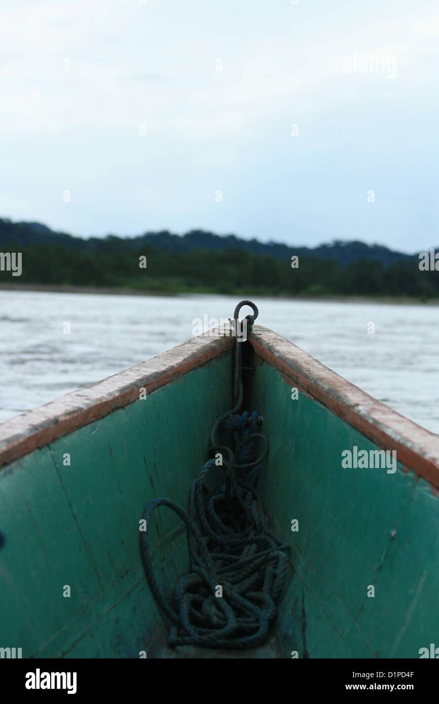 The bow of a long boat traveling down the Napo river in the Ecuadorian rain forest near Tena, Ecuador - Stock Image