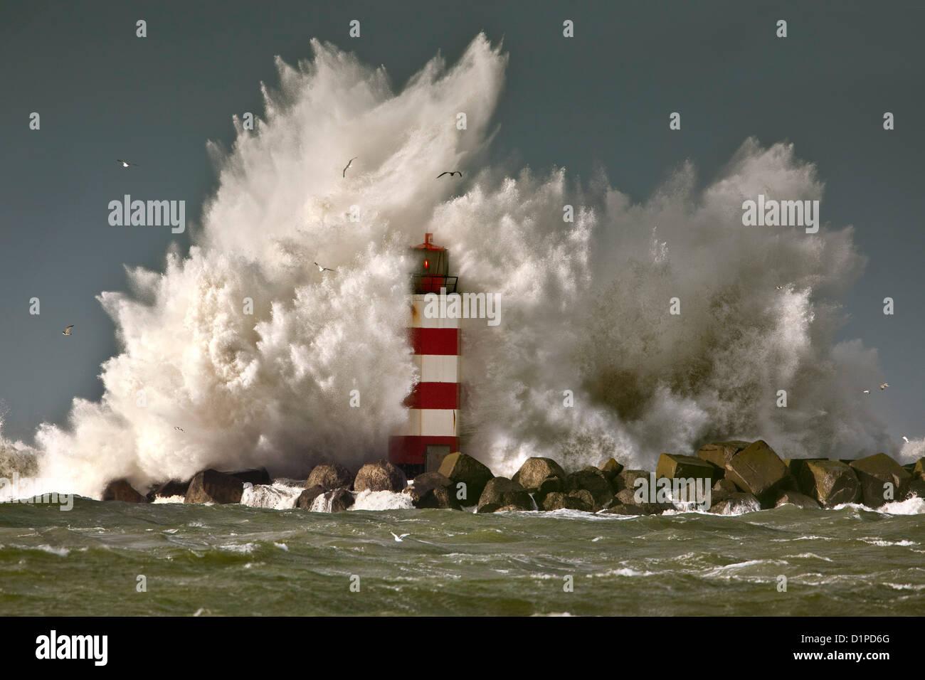 The Netherlands, IJmuiden, Storm. Waves crash against lighthouse or beacon. - Stock Image