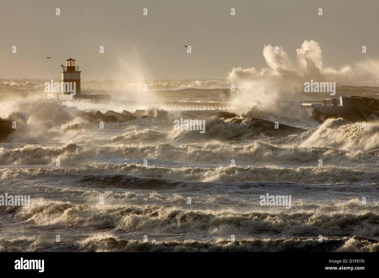 The Netherlands, IJmuiden, Storm. Waves smash against lighthouse or beacon. - Stock Image