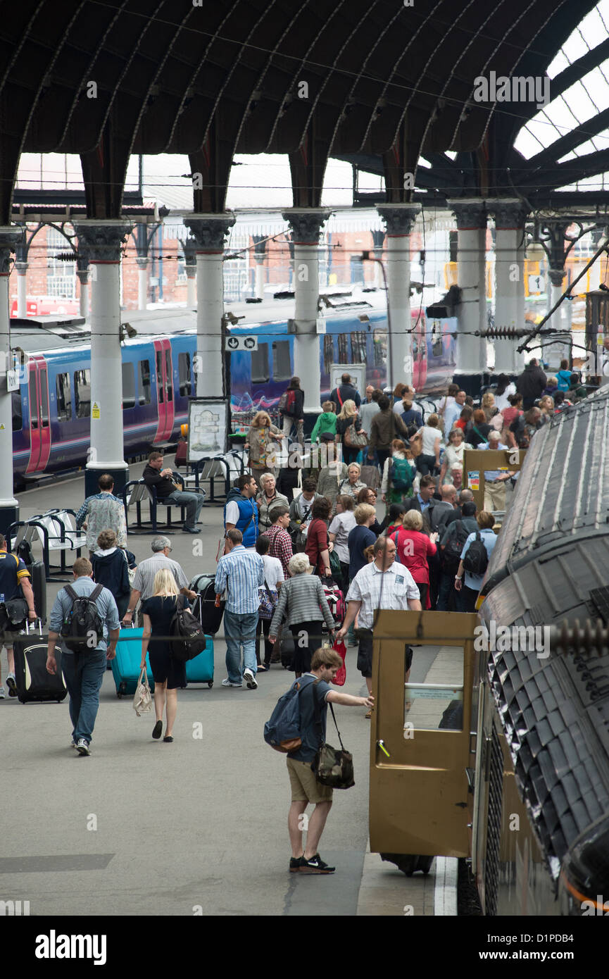 People waiting to board a Grand Central train at York Railway Station, England. - Stock Image