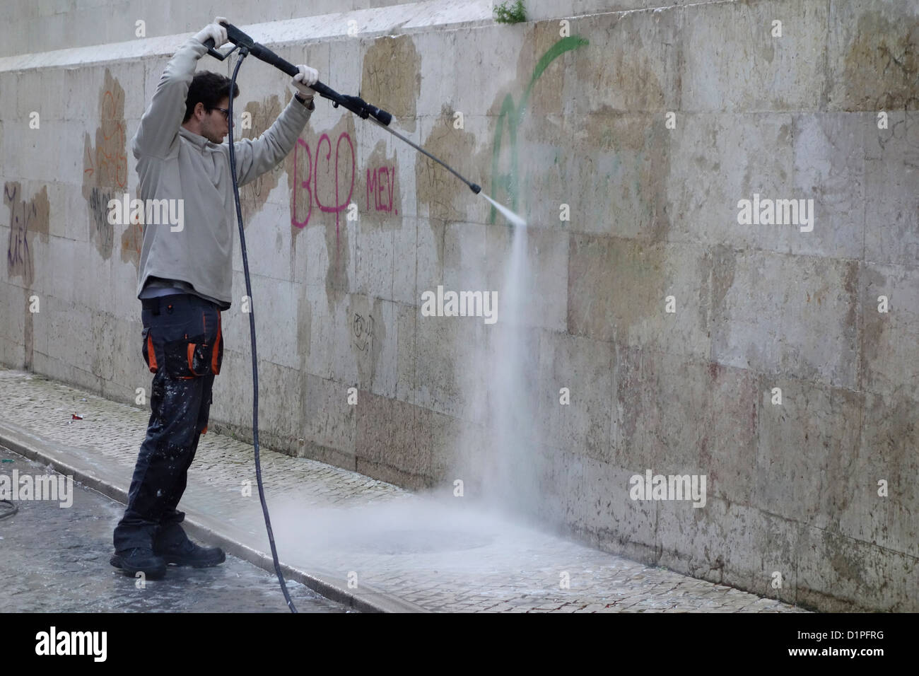 remove grafitti spray vandalism lisbon portugal - Stock Image
