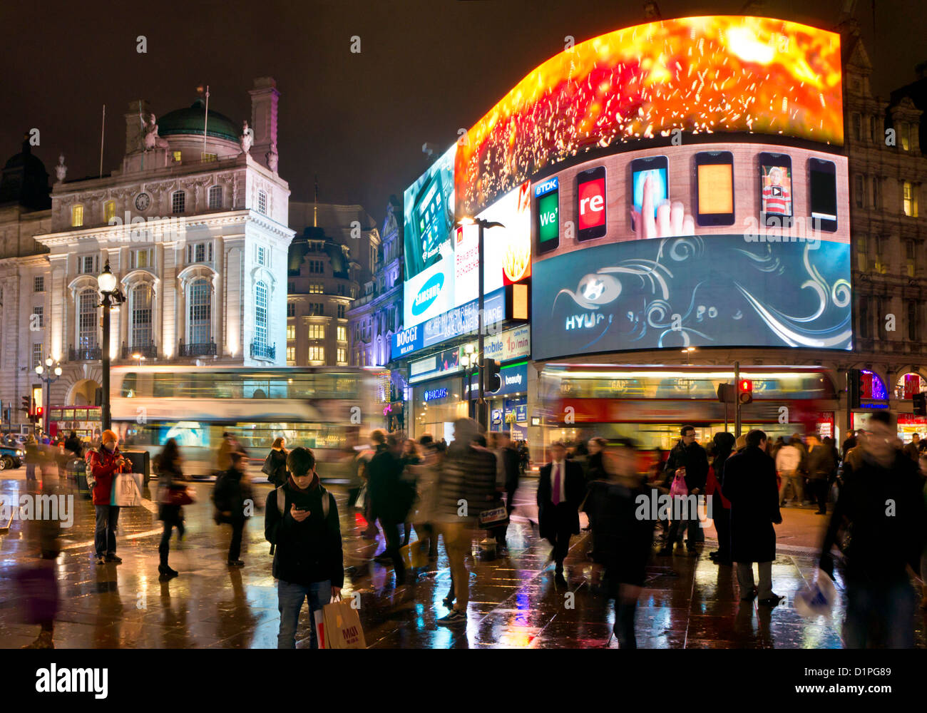 People and London buses on a Busy night in Piccadilly Circus Central London England GB UK EU Europe - Stock Image