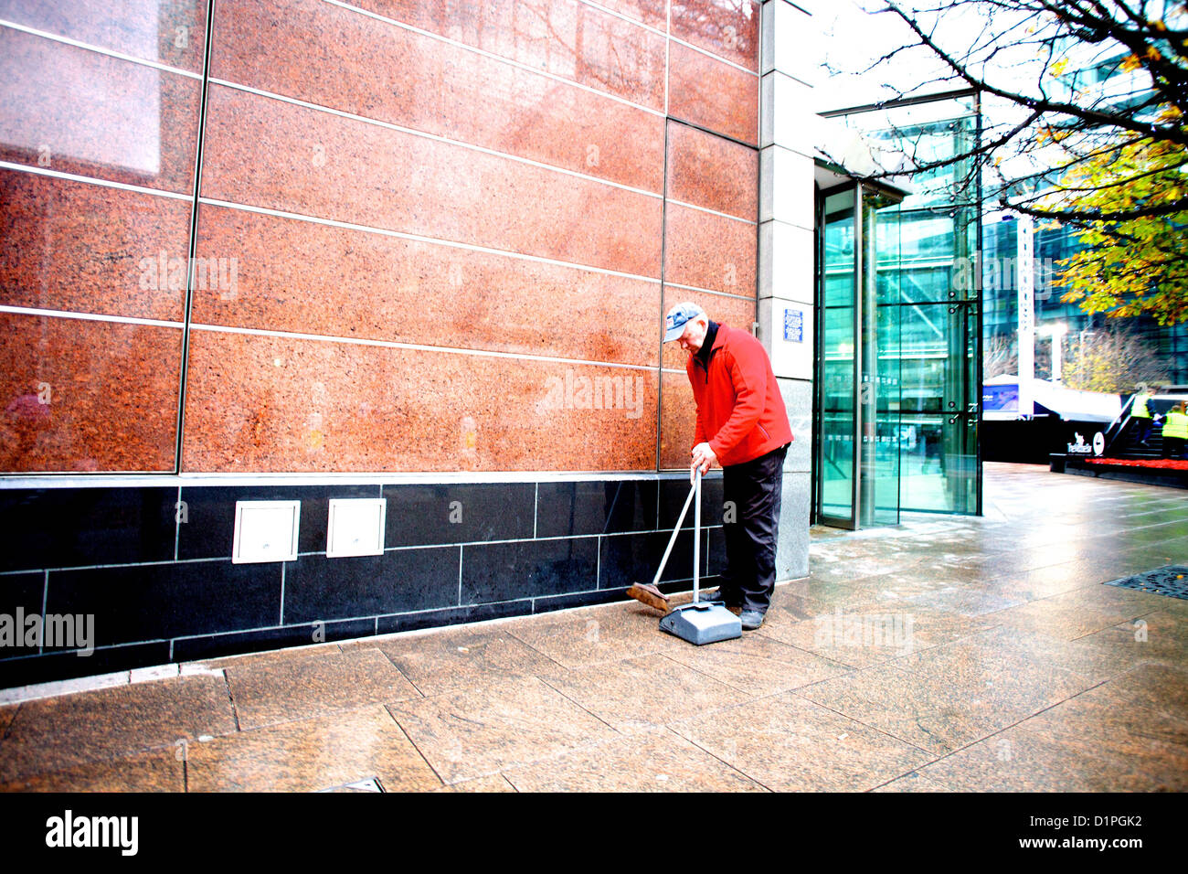 Elderly man in red jacket sweeping rubbish into container around an office block in Canary Wharf, London. - Stock Image