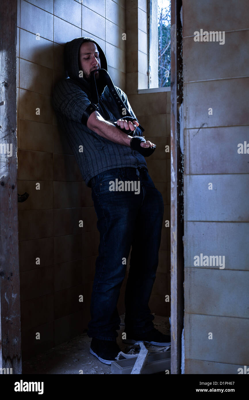 Drug Addict Injecting Heroin in Abandoned Building - Stock Image