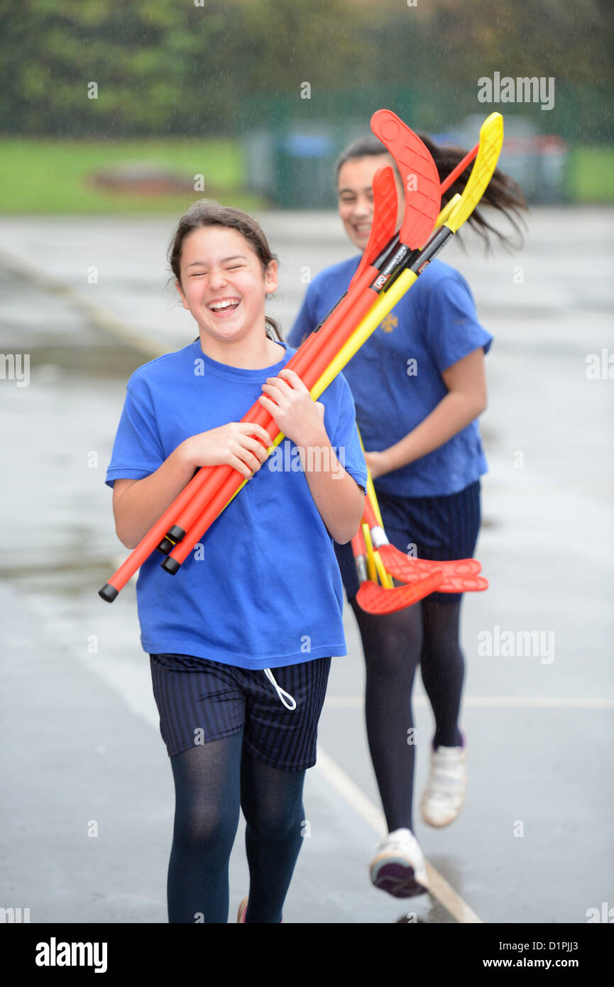 School girls rush inside from the rain carrying hockey sticks at Our Lady & St. Werburgh's Catholic Primary - Stock Image